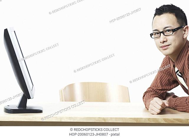 Portrait of a businessman leaning against a table in front of a flat screen monitor