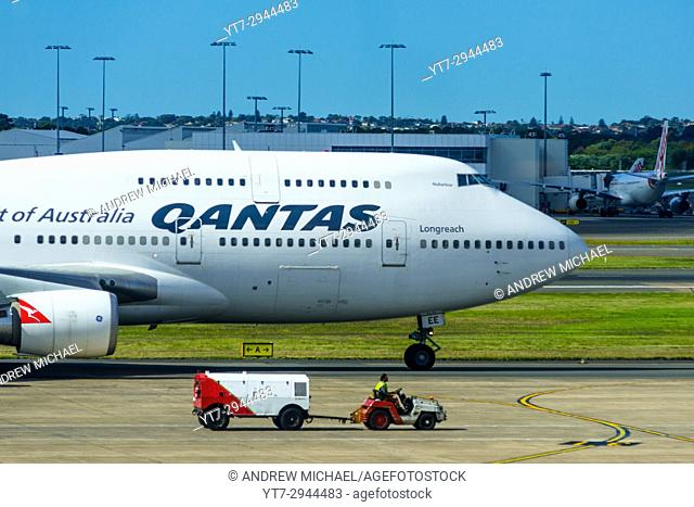 A Qantas 747 jumbo jet next to a baggage vehicle at Sydney international airport, New South Wales, Australia