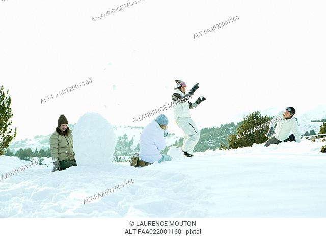 Young friends throwing snowballs at each other, full length