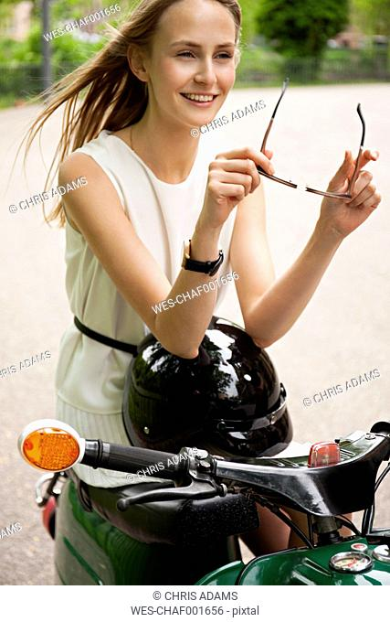 Portrait of smiling young woman with moped and motorcycle helmet