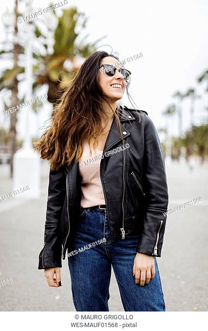 Spain, Barcelona, happy young woman standing on promenade with palms