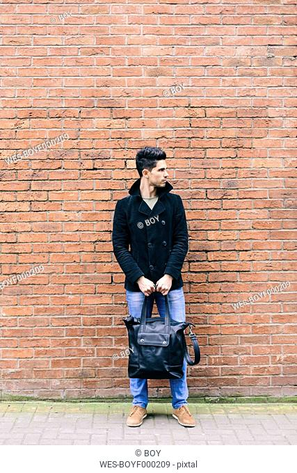 Young casual businessman leaning on brick wall carrying shoulder bag