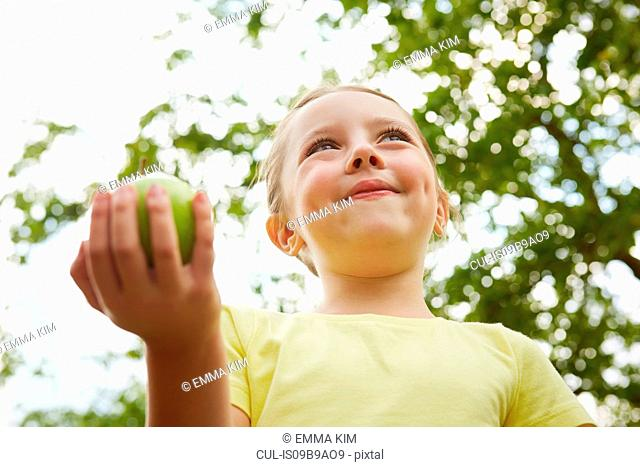 Young girl, outdoors, holding apple, low angle view