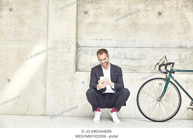 Smiling businesssman with bicycle at concrete wall looking at cell phone