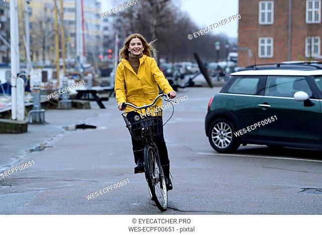 Denmark, Copenhagen, happy woman riding bicycle on waterfront promenade in rainy weather