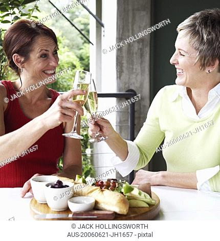 Close-up of two mature women toasting with champagne flutes