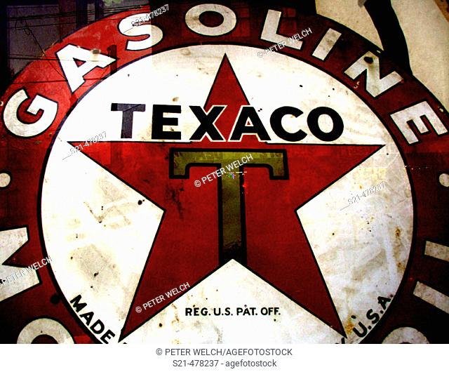 An old Texaco Filling Station sign is captured through the window of an antique store in Upsate, New York. USA