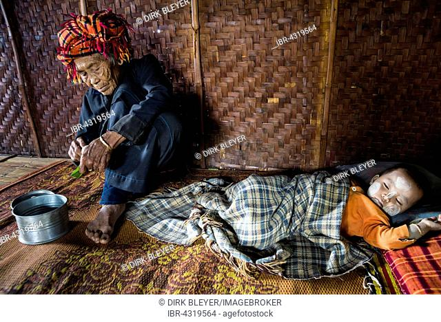 Old woman and sleeping child with thanaka paste in the face of hill tribe Pa-O or Pa-Oh or Pao or Black Karen or Taungthu or dew-soo, ethnic minority