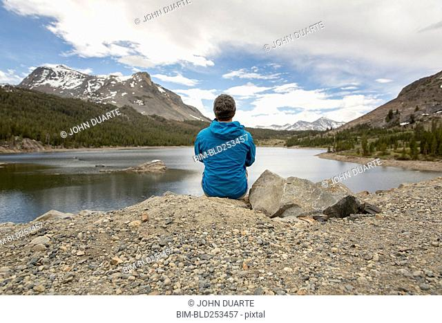 Caucasian man sitting on rock near lake