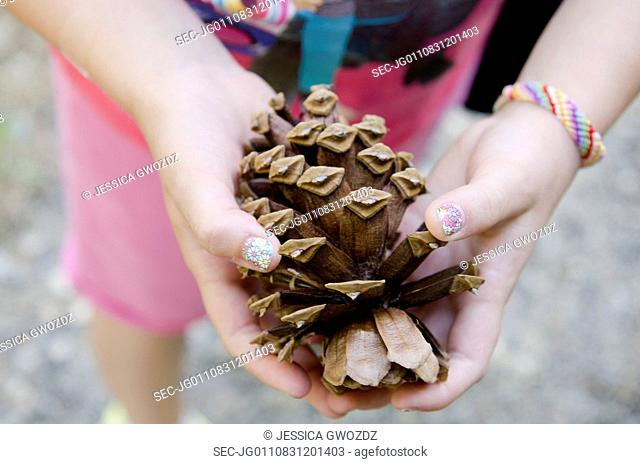 Girl (8-9) holding cone in hands