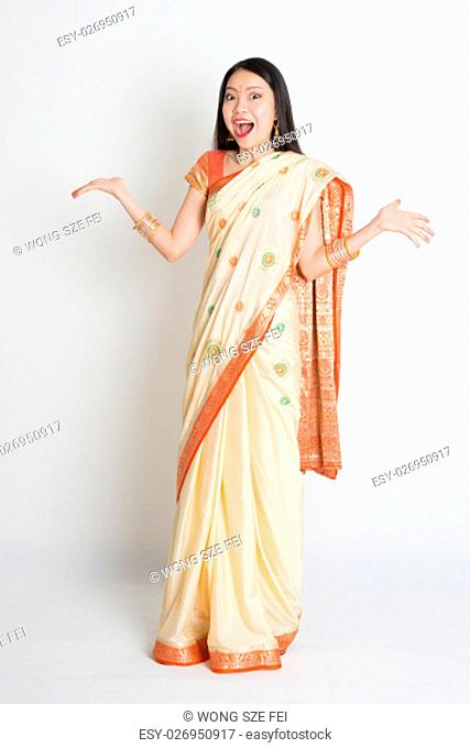 Portrait of surprised young mixed race Indian Chinese female in traditional sari dress, full length on plain background