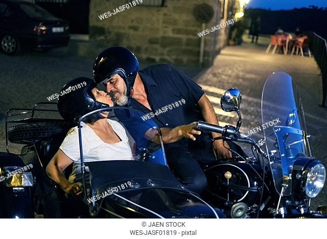 Spain, Banos de la Encina, mature couple on motorcycle with a sidecar kissing at night