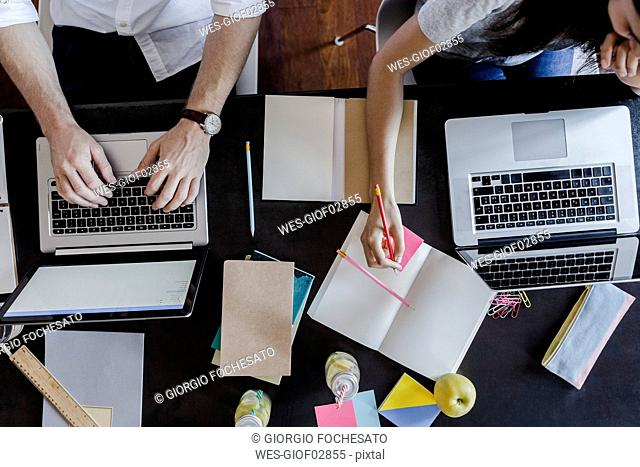 Top view of man and woman using laptops and taking notes