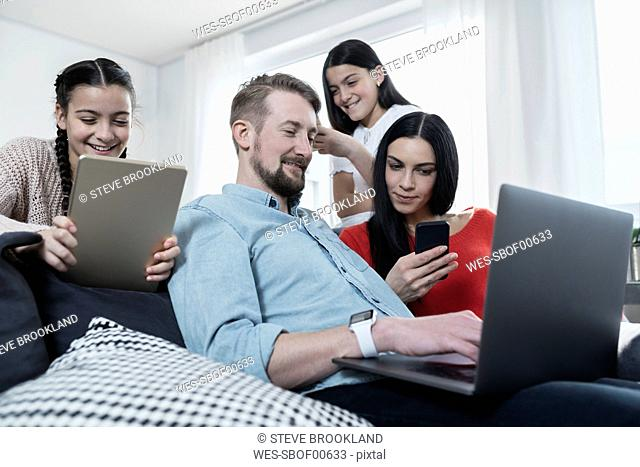 Parents and twin daughters on sofa using portable devices
