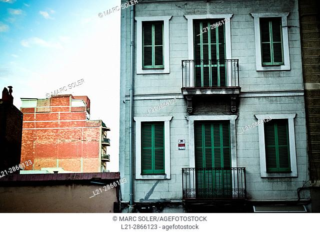 Old building apartment with green facade. Closed balconies, closed windows. Barcelona, Catalonia, Spain