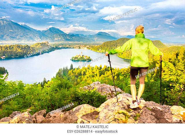 Young spoty active lady with hiking sticks admiring beautiful nature around Bled Lake in Julian Alps, Slovenia