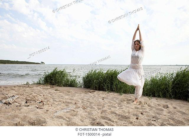 Young woman practicing yoga on sea shore against sky
