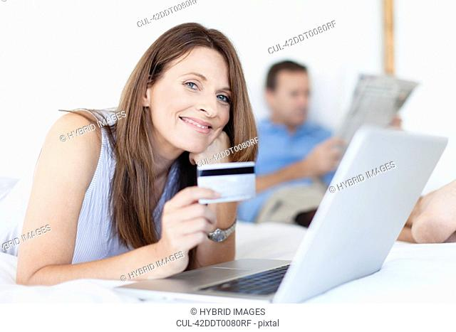 Woman shopping online on bed