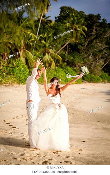 newlyweds with wedding bouquet of jasmine on the beach in the Seychelles