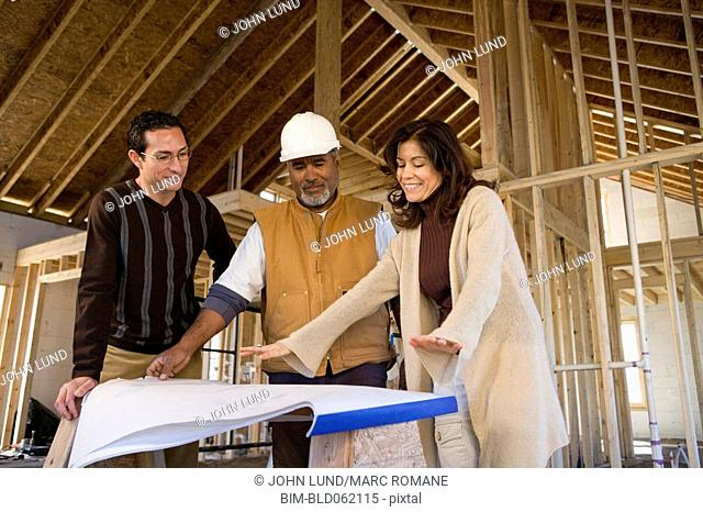 Hispanic couple and construction worker at new construction site