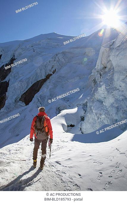 Caucasian hiker standing on snowy mountain