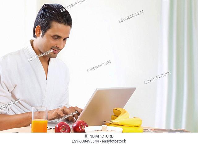 Man using laptop at breakfast table