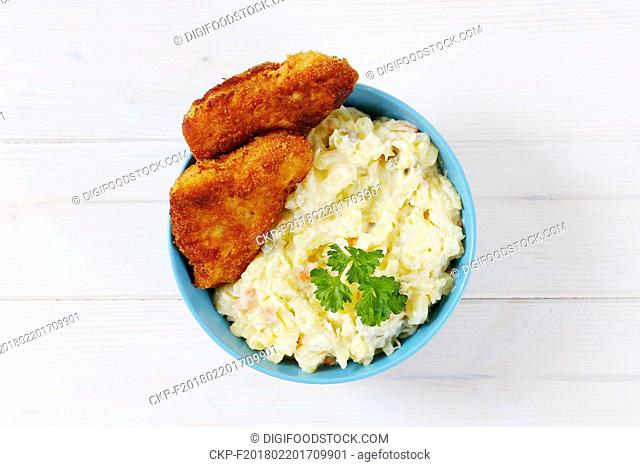 breaded schnitzels with potato salad in turquoise bowl