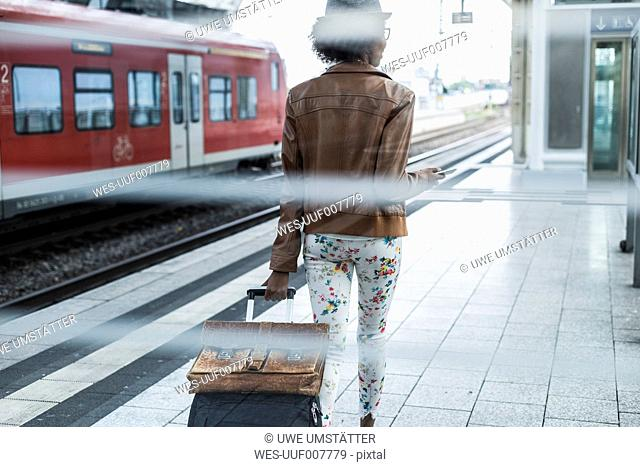 Back view of young woman with trolley bag and briefcase at platform