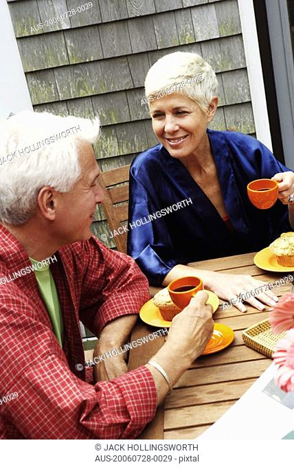Mature man and a senior woman sitting at the table and talking to each other