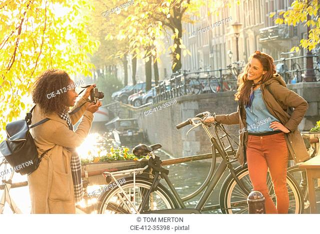 Young woman photographing friend with bicycle along autumn canal, Amsterdam