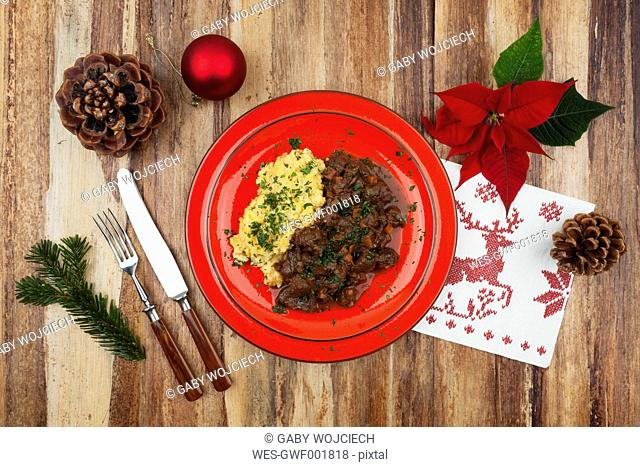 Plate of cooked venison goulash with mashed potatoes and Christmas decoration on wooden background