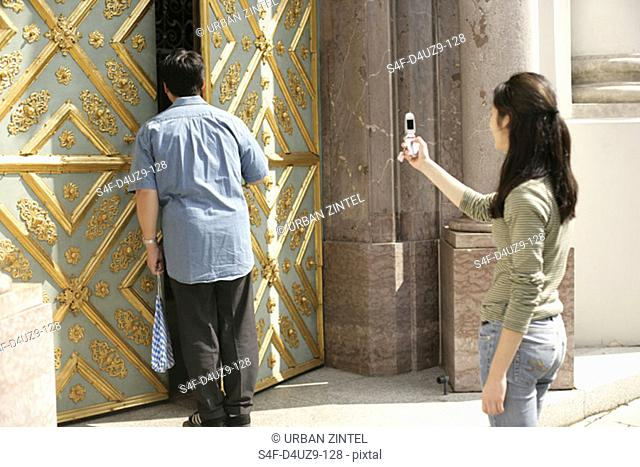 Female taking a picture of an Asian man who is about to enter an ornate door, selective focus