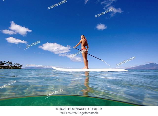 Healthy Maui girl stand-up paddles at Napili Bay, Maui, Hawaii