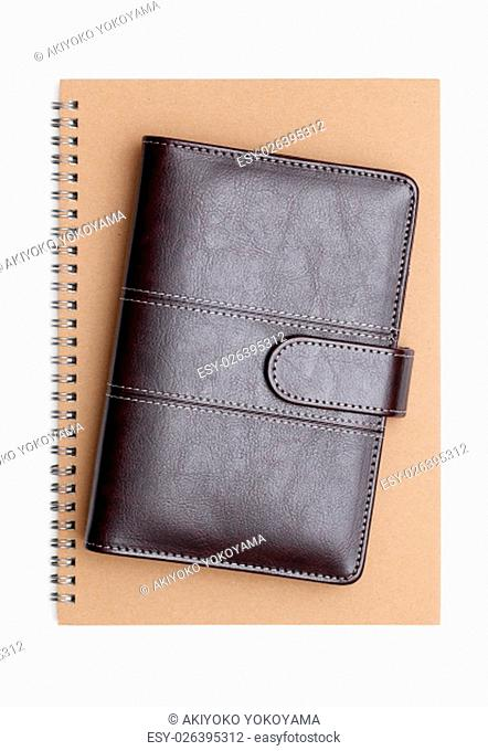 brown leather organizer and spiral notebook
