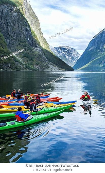Gudvangen Norway fjord called Naeroyforden Fjord college students getting lesson to paddle colorful kayaks in water MR-7