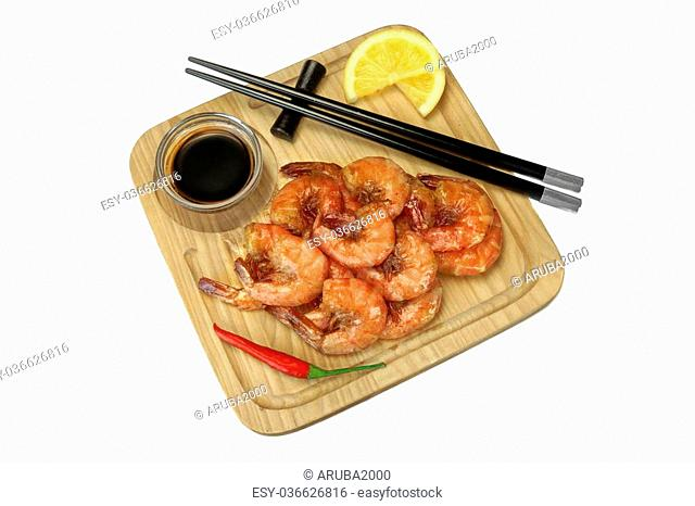 Grilled Red King Size Shrimps Or Prawns With Sauce, Chili Pepper and Lemon, Served With Wood Chopsticks On Wood Board Isolated On White Background, Close Up