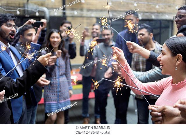 Friends celebrating with sparklers at party