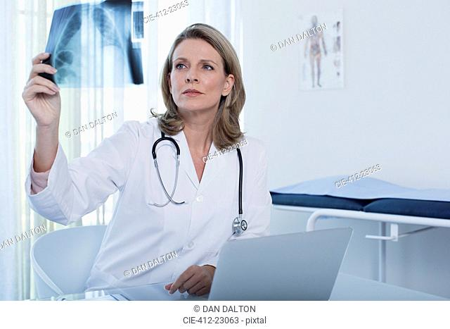 Female doctor looking at x-ray at desk with laptop in office