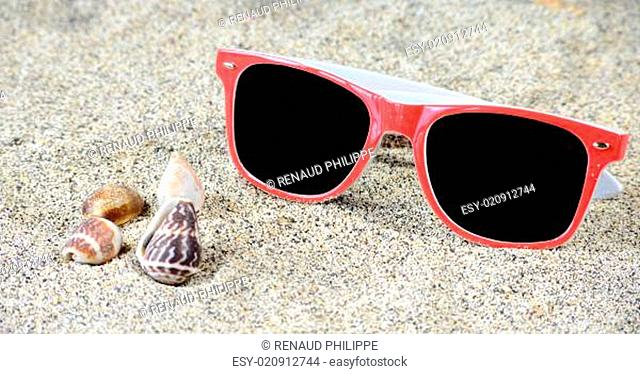 Red sunglasses on sand
