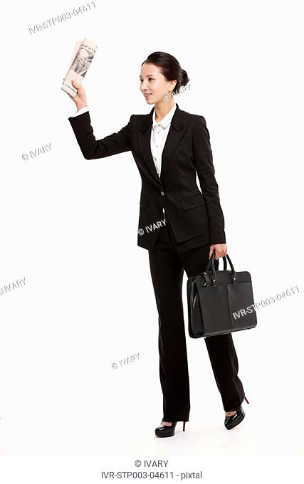 A young businesswoman posing in a studio with a newspaper and a briefcase