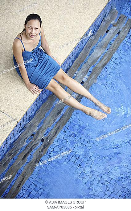 Young woman sitting by swimming pool, dipping feet in water, looking at camera