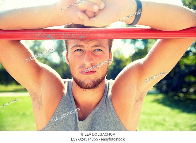 fitness, sport, training and lifestyle concept - young man with heart-rate watch bracelet exercising on horizontal bar in summer park
