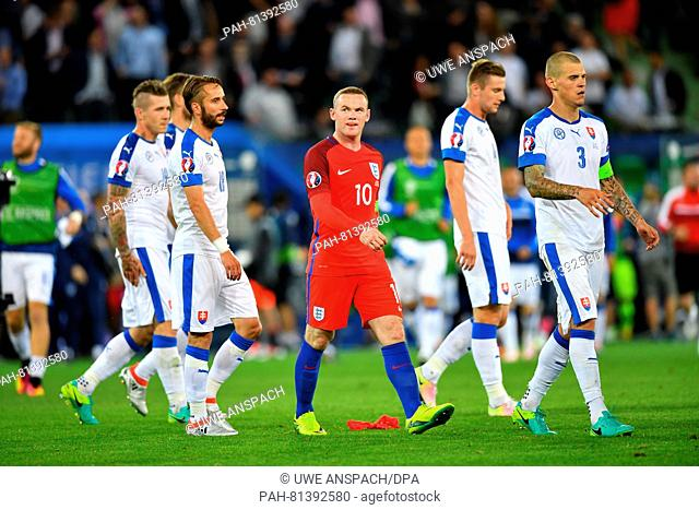 Wayne Rooney (c) of England is surrounded by Slovakian players as he leaves the pitch at the preliminary round Group B match between Slovakia and England at...