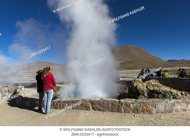 Tourists looking at the steam rising from hot springs at El Tatio Geysers geothermic basin near San Pedro de Atacama in the Atacama Desert, northern Chile