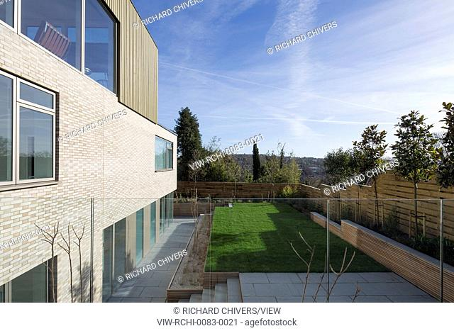 View of garden and south facade. Private Houses Withdean Road, Brighton, United Kingdom. Architect: John Pardey Architects, 2017
