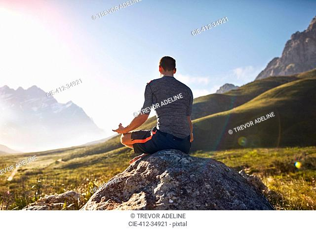 Young man meditating on rock in sunny, remote valley