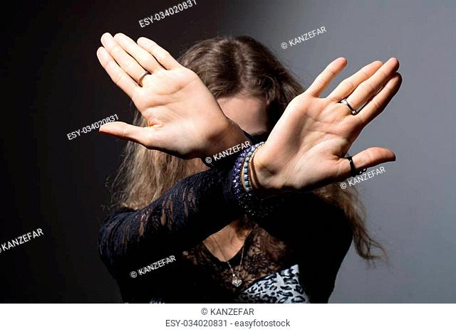 Out of focus woman with her hands signaling to stop isolated on a black background
