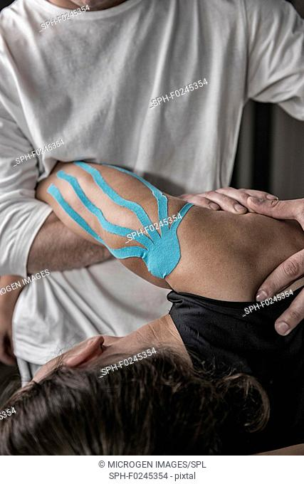 Physical therapist stretching shoulder
