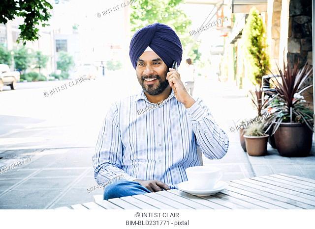 Man wearing turban talking on cell phone at cafe
