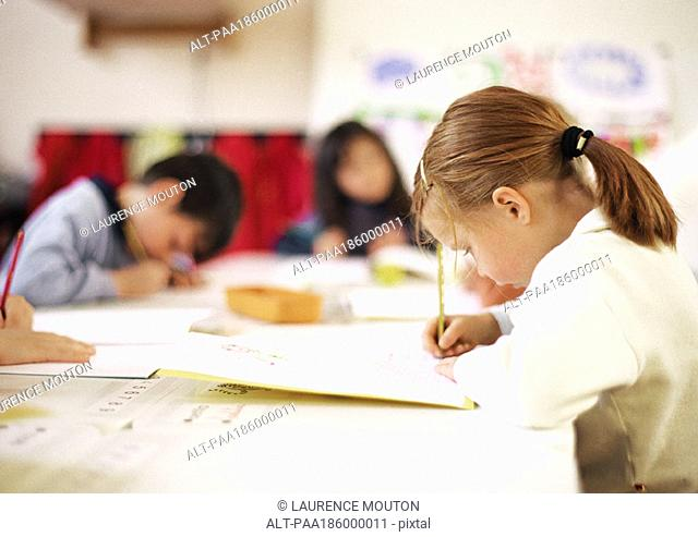Children sitting at table, writing